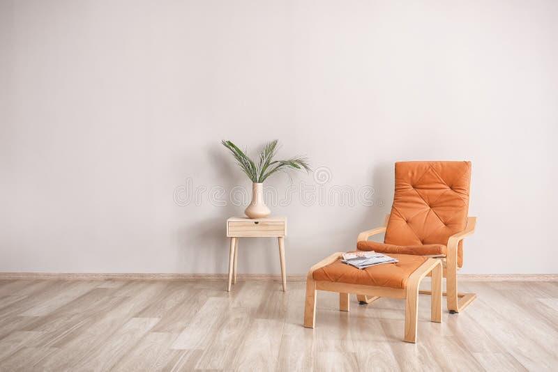有扶手椅子、立场和绿色叶子的客厅在轻的墙壁附近的花瓶 图库摄影