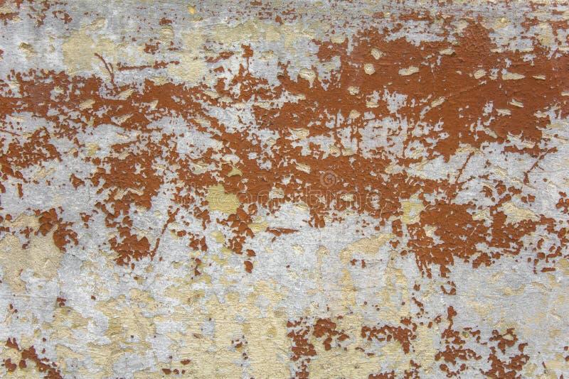 有抓痕和棕色红色剥的油漆的老破旧的灰色白色混凝土墙 E 库存图片