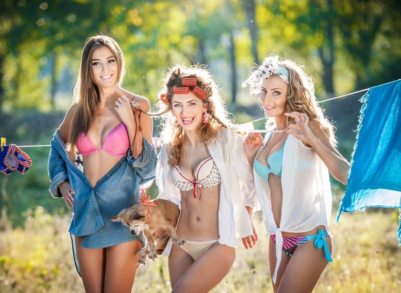 有投入衣裳的诱惑成套装备的三名性感的妇女烘干在太阳 笑肉欲的年轻的女性投入洗涤物 免版税库存照片