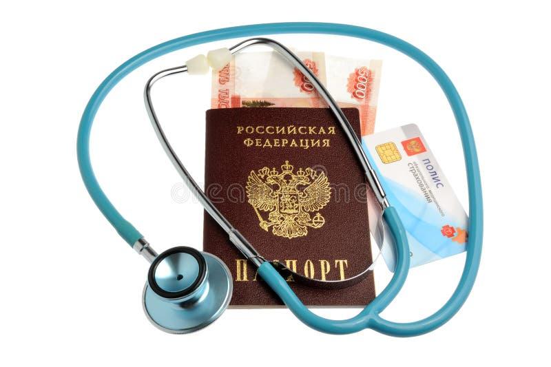 有护照、金钱和医疗保险政策的听诊器是 库存照片