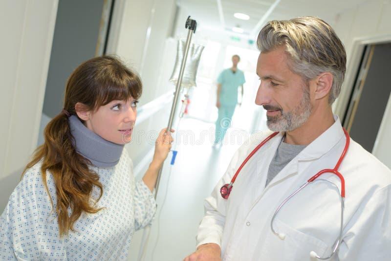 有护颈垫和便携式的滴水的病人谈话与走廊的医生 免版税图库摄影
