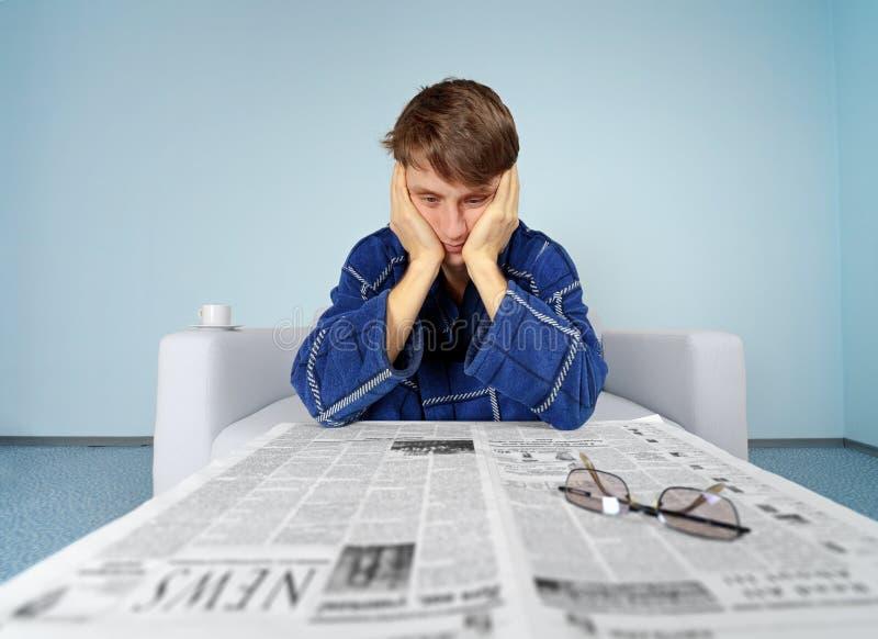 有报纸的人-困难找到工作 免版税库存照片