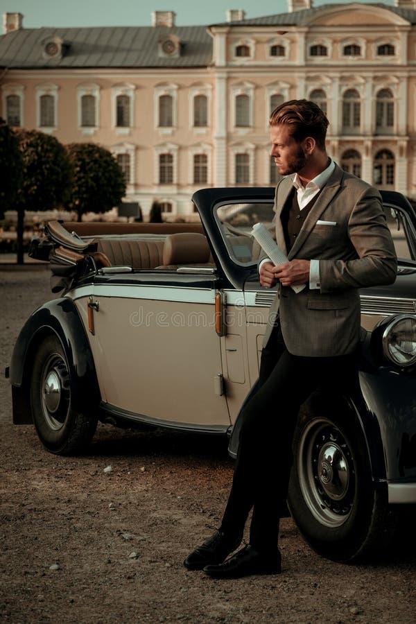有报纸的确信的富裕的年轻人在经典敞篷车附近 免版税图库摄影