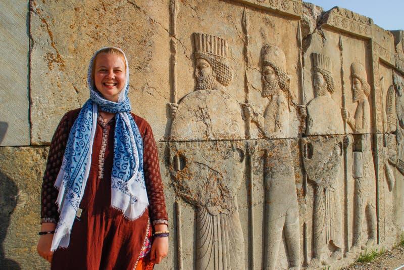 有报道的头的年轻女人游人在波斯伊朗- P的天首都的著名浅浮雕的背景站立 免版税库存照片