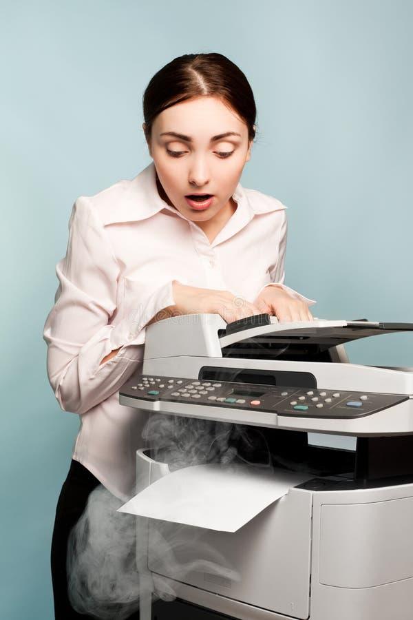 有抽烟的影印机的女实业家 免版税库存照片