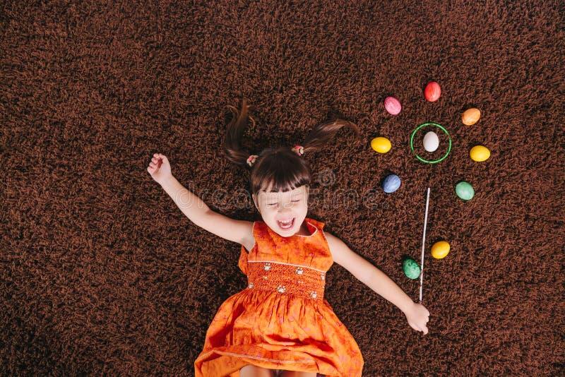 有抽象花的愉快的小女孩 复活节aggs 顶视图 库存图片