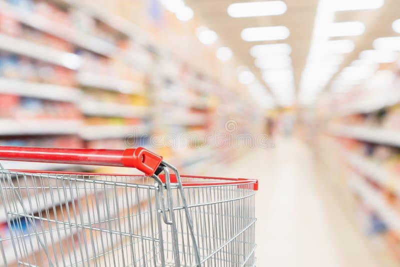 有抽象迷离超级市场廉价商店走道和产品架子内部的空的手推车 免版税库存图片