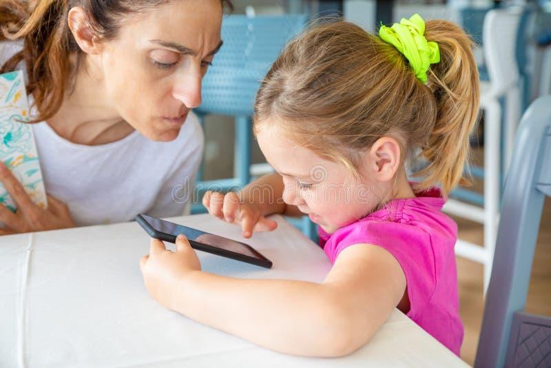 有担心的面孔的母亲观看她的女儿的冲浪在机动性 库存照片