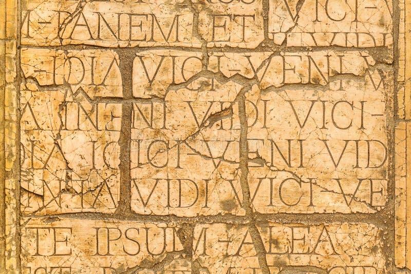 有拉丁题字和罗马字母的破裂的墙壁。 图库摄影