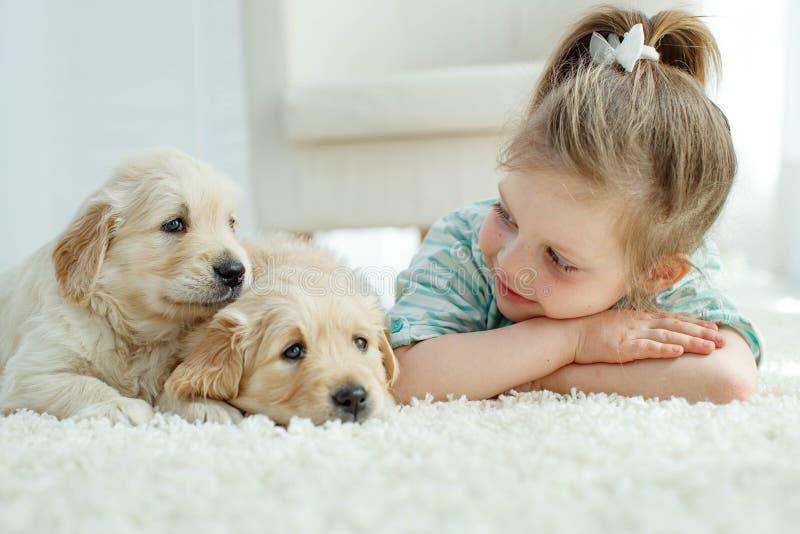 有拉布拉多小狗的孩子在家在地毯 免版税库存图片