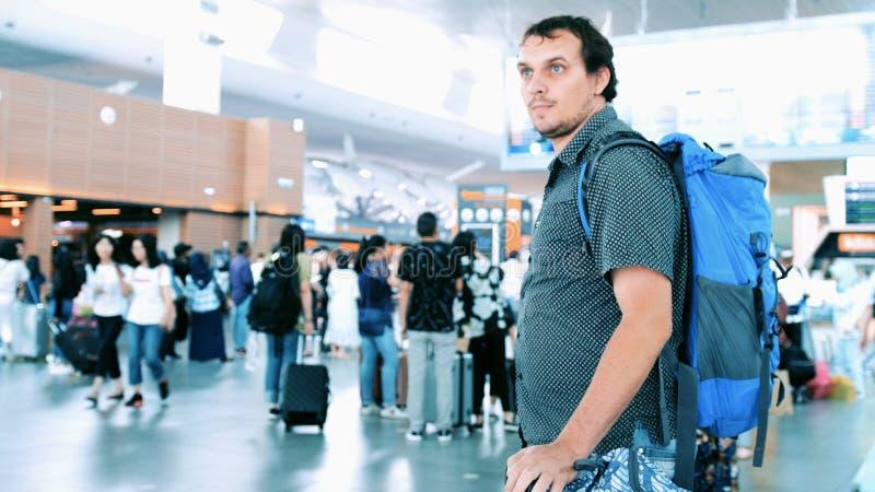 有拉扯手提箱的背包的年轻有胡子的人在现代机场终端 旅行的帅哥轻易获胜 免版税库存照片