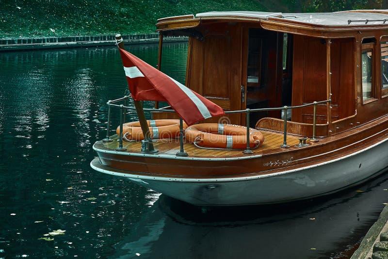 有拉脱维亚航行国旗的一条小船在拉脱维亚全国歌剧附近的公园在里加,拉脱维亚 库存照片
