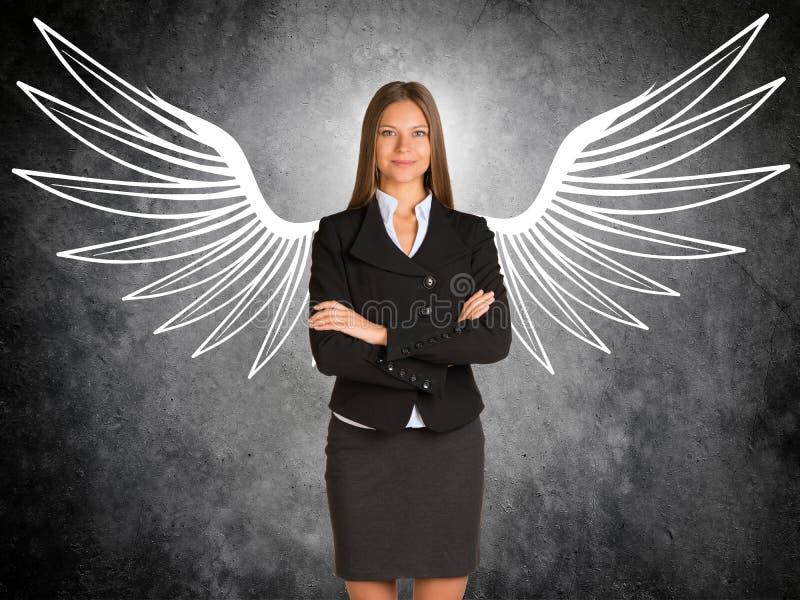 有拉长的天使翼的女实业家 免版税库存图片