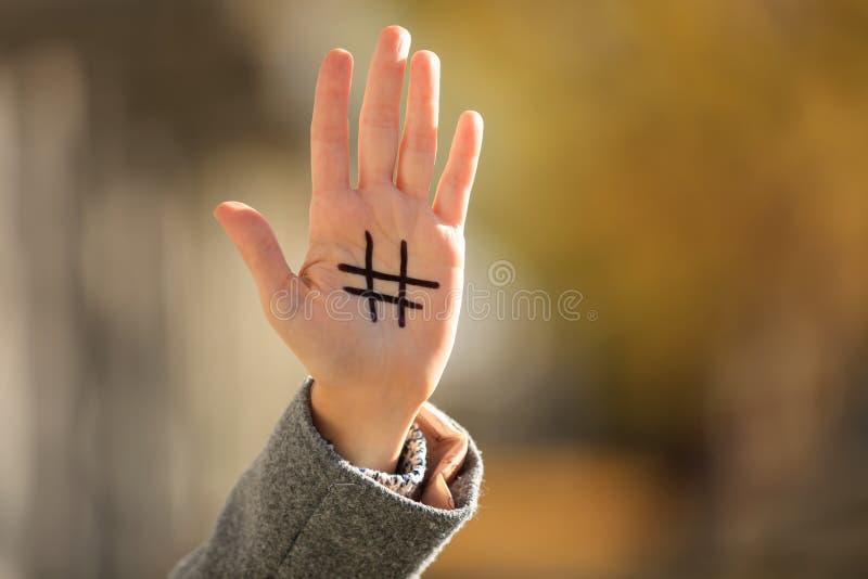 有拉长的hashtag标志的妇女在她的手上户外 库存图片