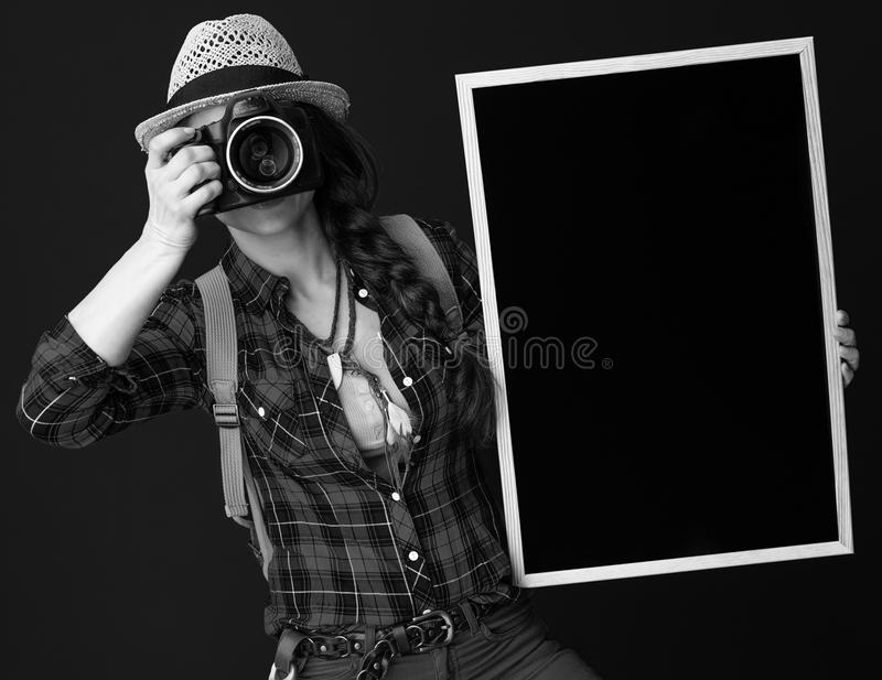 有拍与数字照相机的黑板的旅行家妇女照片 库存照片