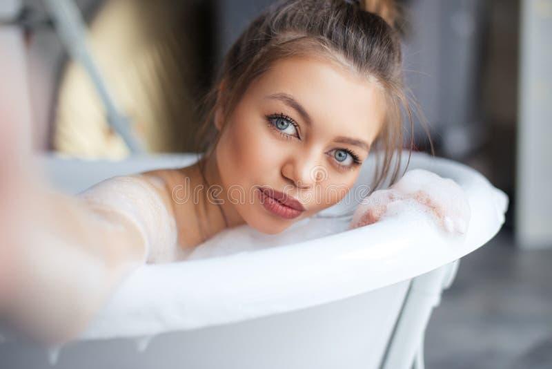 有拍在浴的充分的嘴唇的美丽的棕色毛发的女孩自已照片 图库摄影