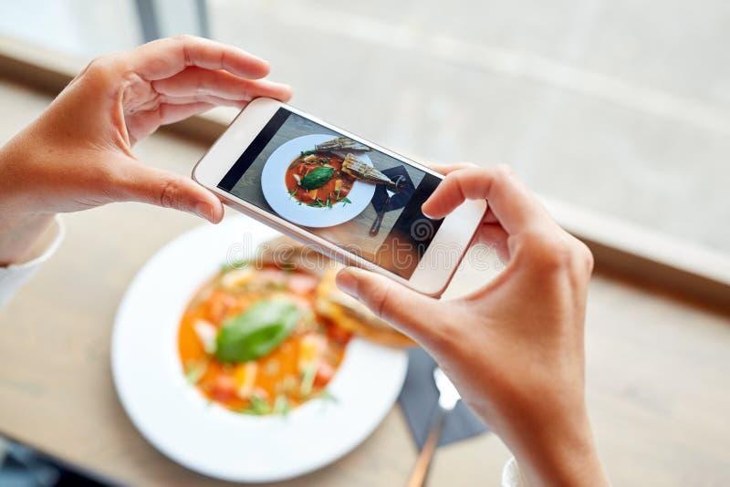 有拍摄食物的智能手机的手 免版税库存图片