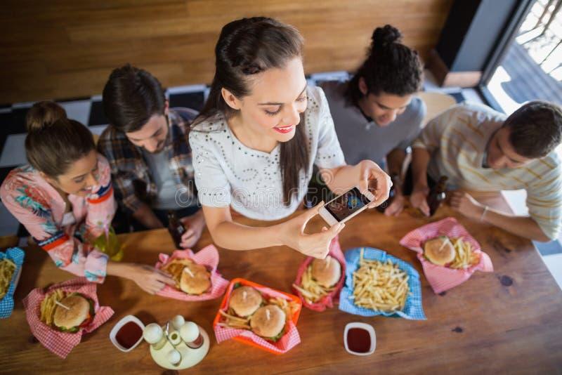 有拍摄食物的朋友的妇女在餐馆 库存图片