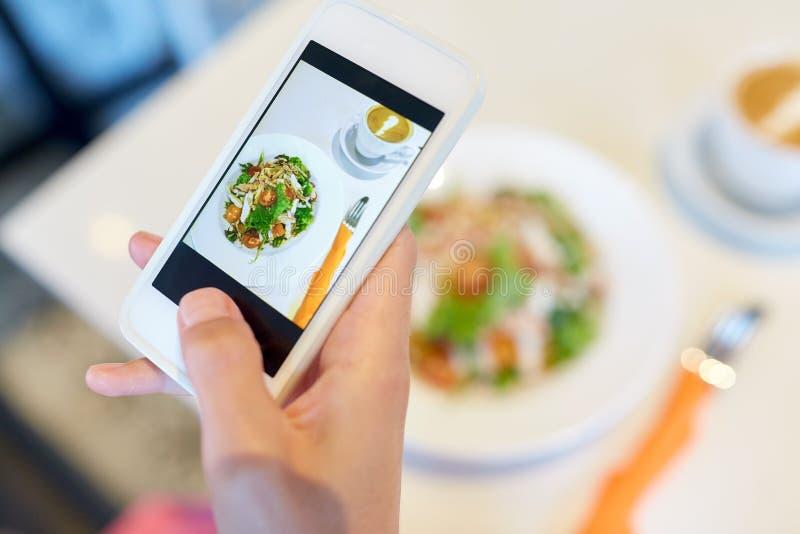有拍摄餐馆食物的智能手机的手 库存图片