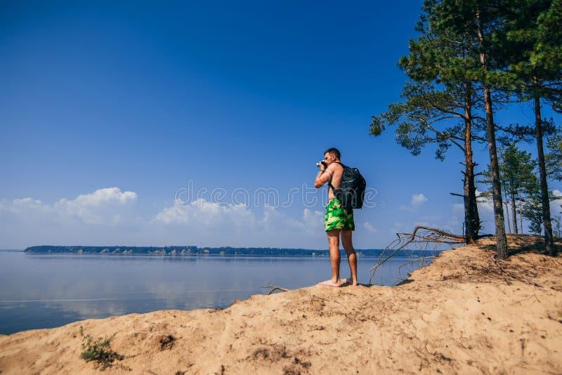 有拍照片的背包的旅客摄影师 免版税库存图片