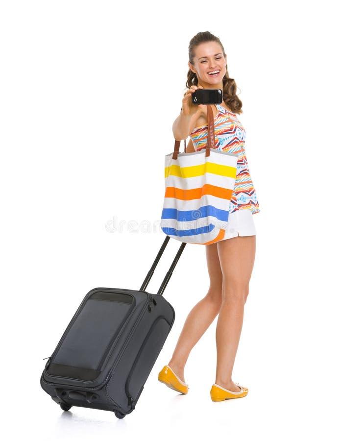 有拍照片的轮子袋子的愉快的旅游妇女 免版税库存照片