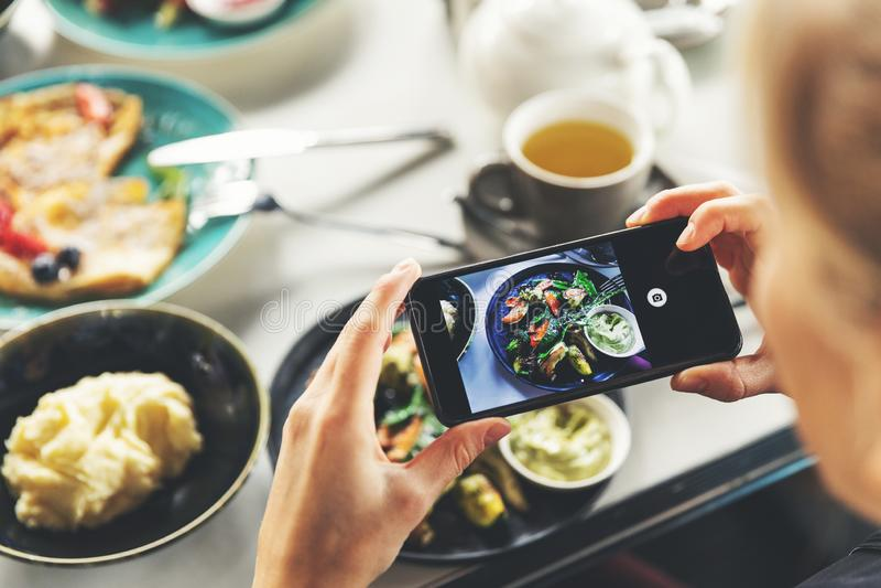 有拍食物的照片巧妙的电话的妇女在餐馆 库存照片