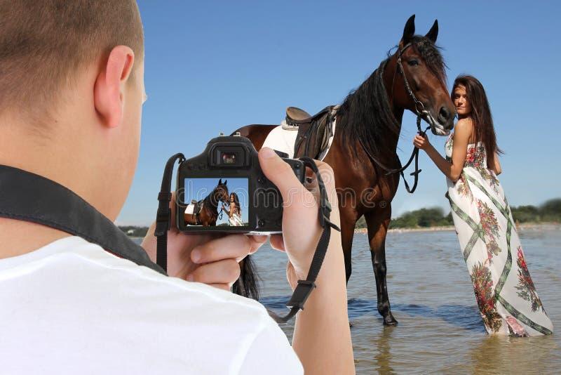 有拍年轻美丽的妇女的照片h的照相机的人 免版税库存图片