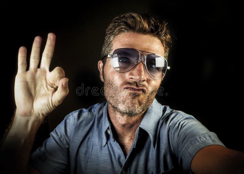 有拍selfie与手机照相机smi的太阳镜和现代行家看起来的疯狂的愉快和滑稽的人自画象照片 免版税库存图片
