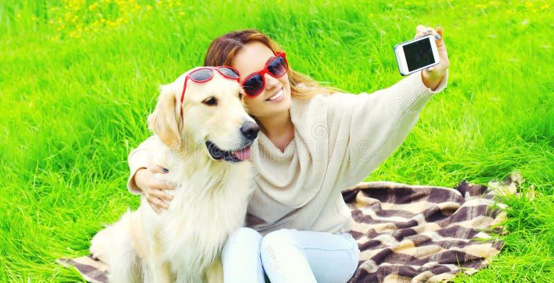 有拍selfie照片的金毛猎犬狗的愉快的微笑的妇女由电话在夏天 免版税库存照片