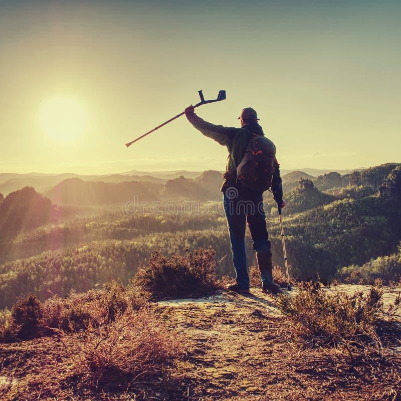 有拐杖的废人在岩石站立 在足迹手段的步行 库存照片