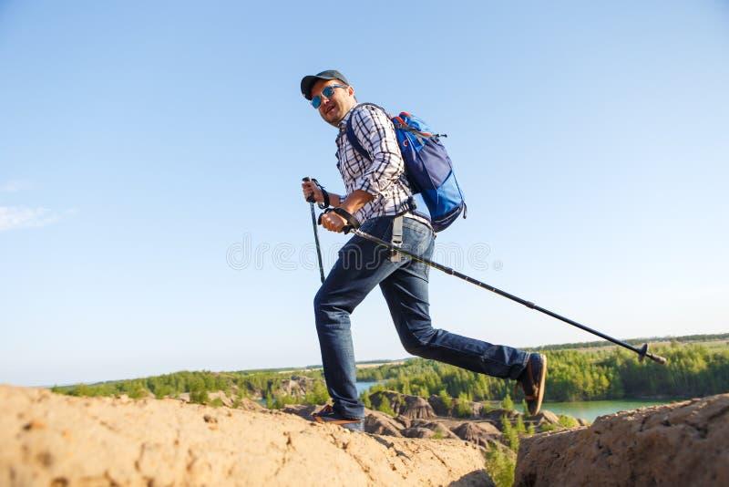 有拐杖的走在山区的年轻旅游人的图象 库存图片