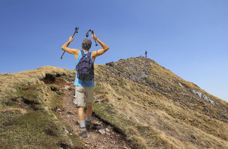 有拐杖的登山家,远足往山山顶 免版税库存图片