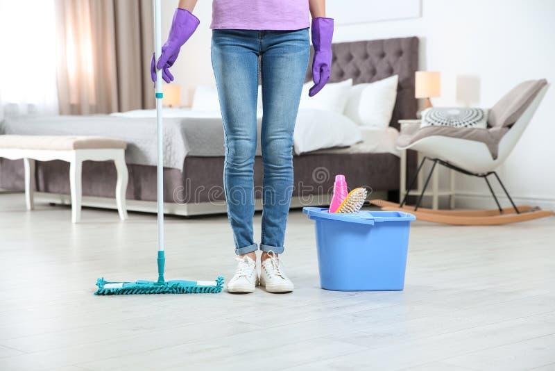 有拖把的年轻女人和洗涤剂在卧室 清洁服务 免版税库存图片