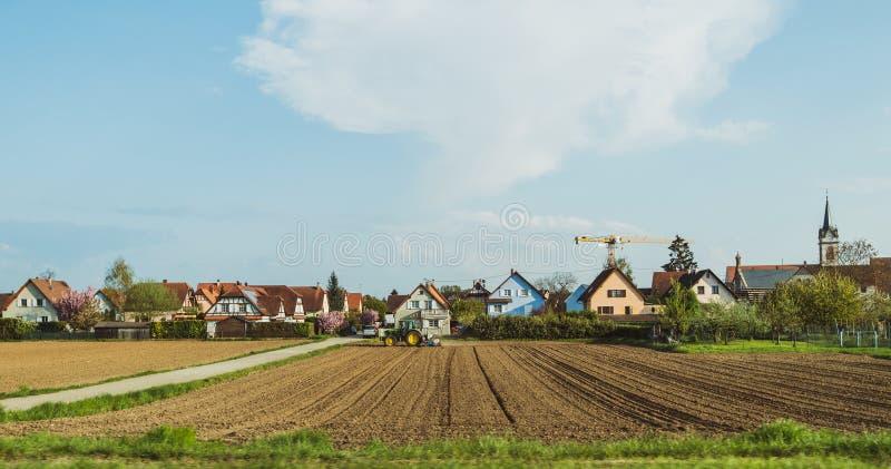有拖拉机工作的美丽的干净的富裕的法国村庄在领域 免版税库存照片