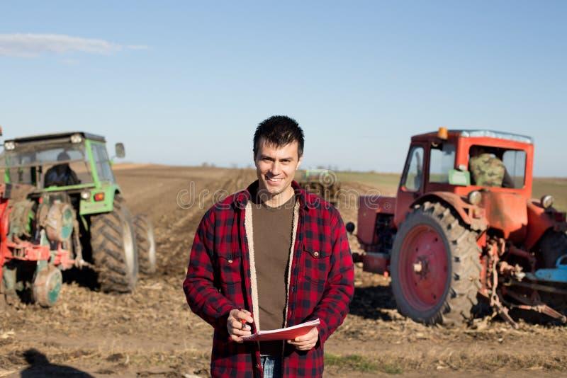 有拖拉机的农夫在领域 免版税图库摄影