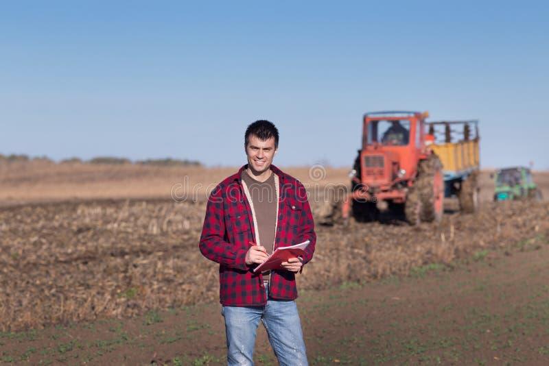 有拖拉机的农夫在领域 库存图片