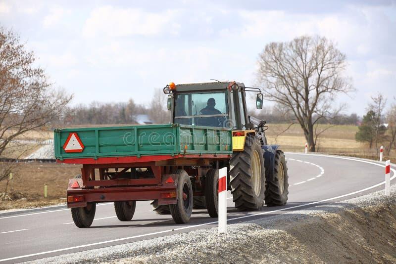 有拖车乘驾的一台拖拉机在柏油路 农业运输背面图  农产品的运输在a的 免版税库存照片
