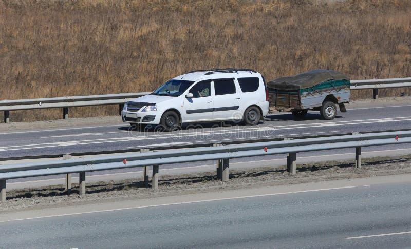 有拖车的汽车在高速公路去 库存照片