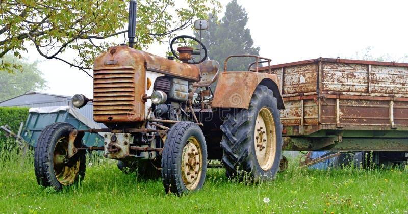 有拖车的老生锈的农用拖拉机 免版税库存照片