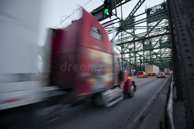 有拖车的被弄脏的红色半卡车在桥梁的高速公路 图库摄影