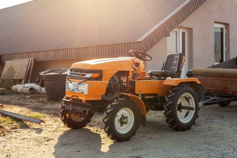 有拖车身分的微型红色拖拉机在农场的飞机棚大厦附近在日落或日出期间 小农业 库存图片