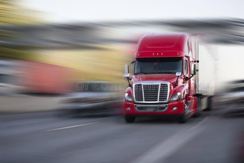 有拖车移动的明亮的红色现代大半半船具卡车与 库存图片