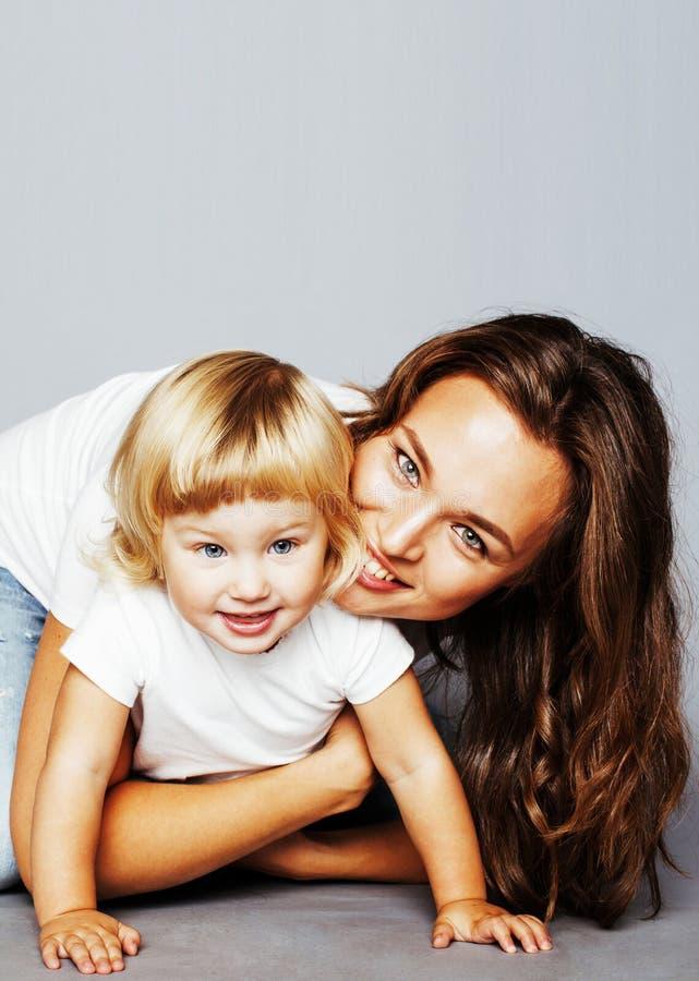 有拥抱一点逗人喜爱的白肤金发的女儿的年轻俏丽的时髦的母亲,愉快的微笑的真正的家庭,生活方式人概念 库存照片