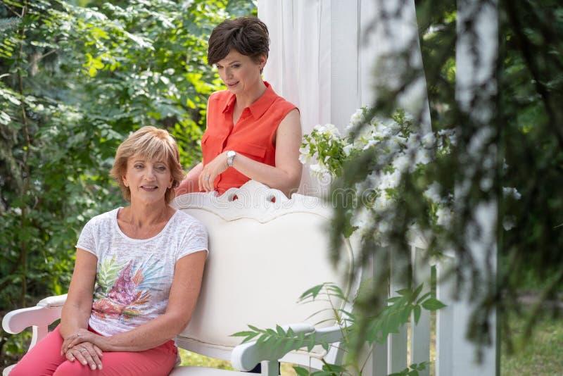 有拥抱她的成人的女儿的母亲微笑和有在室外的长凳的一次交谈 库存照片
