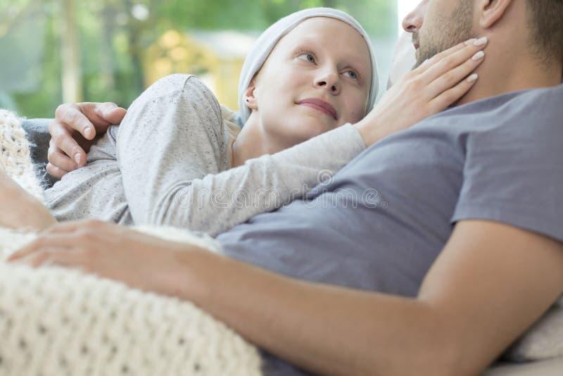 有拥抱她的男朋友的癌症的微笑的女孩,当放松在时 免版税图库摄影