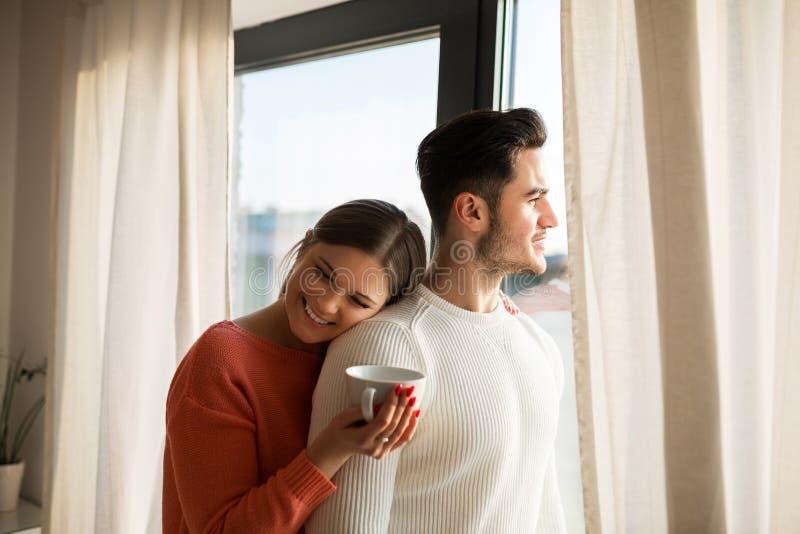 有拥抱对她的男朋友的咖啡的愉快的妇女 库存照片