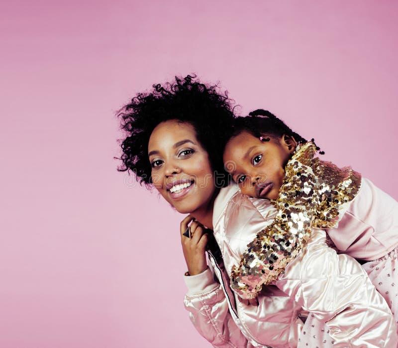 有拥抱小逗人喜爱的女儿的,愉快微笑年轻俏丽的非裔美国人的母亲在桃红色背景,生活方式 免版税库存图片