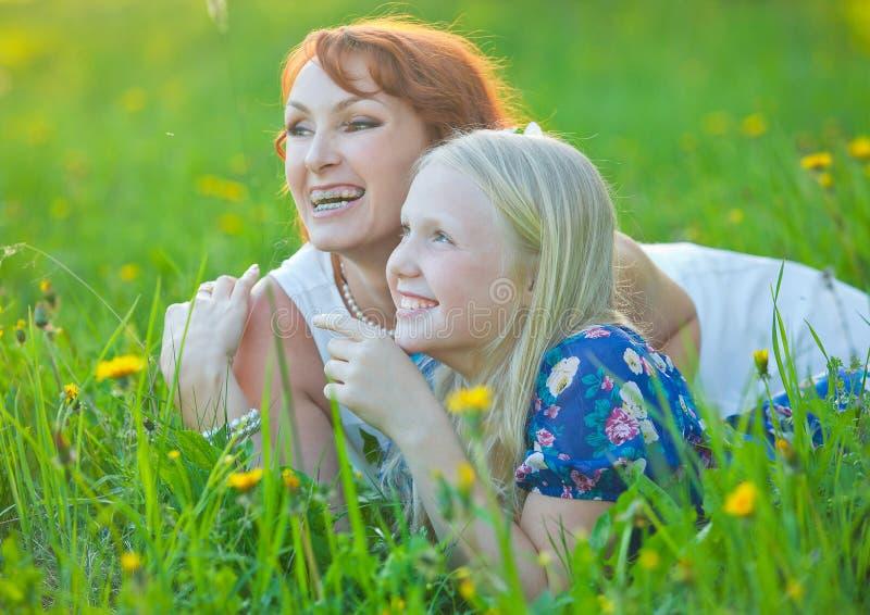 有括号的妈妈和她的小女儿说谎  免版税库存照片