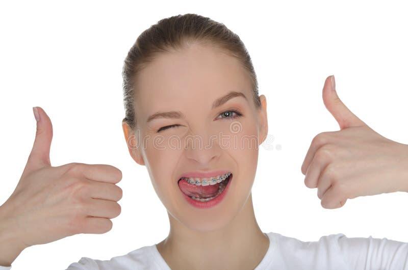 有括号的微笑的愉快的女孩在牙 免版税库存图片