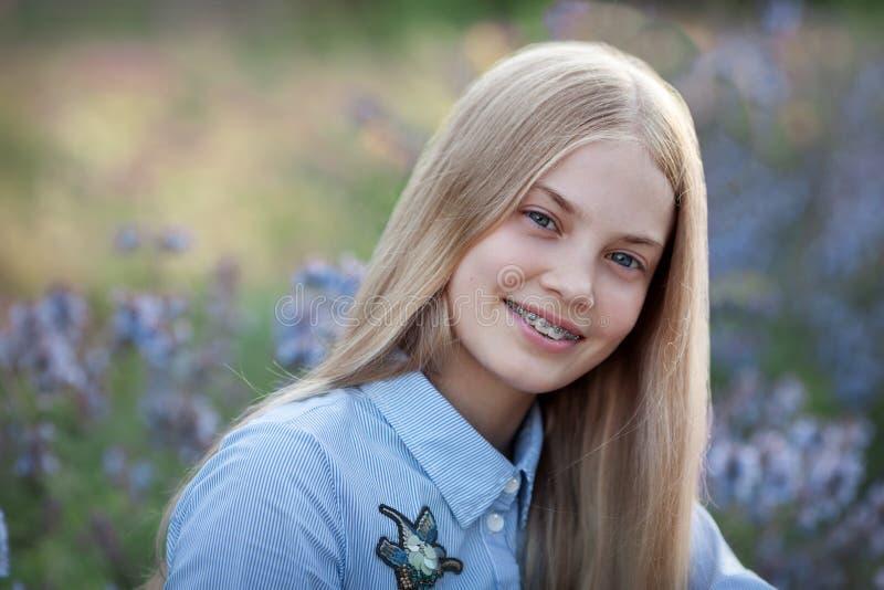 有括号的美丽的青少年的女孩在她牙微笑 白肤金发的模型画象与长发的在蓝色花 免版税图库摄影